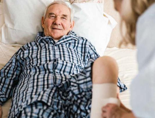 man lying with caregiver