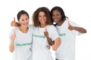 three volunteers showing thumbs up